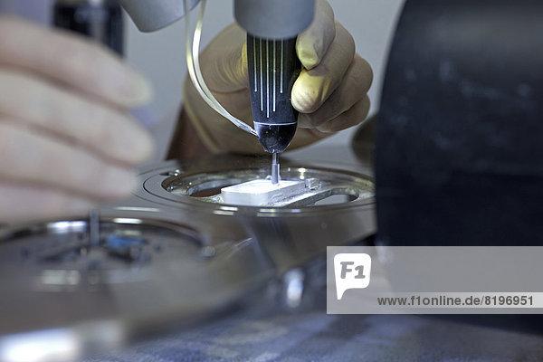 Reifer Mann bereitet Zirkonoxid zur Herstellung von Zahnersatz vor