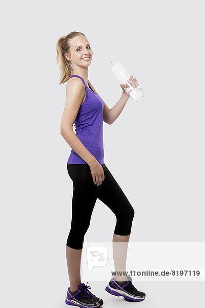 Porträt einer jungen Frau mit Wasserflasche  lächelnd
