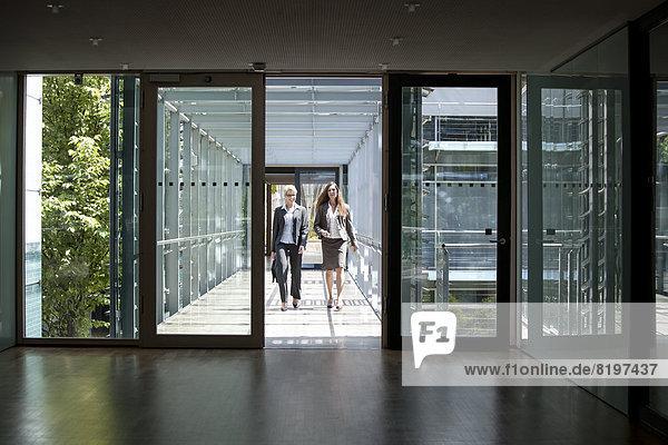 Two businesswomen walking in office building