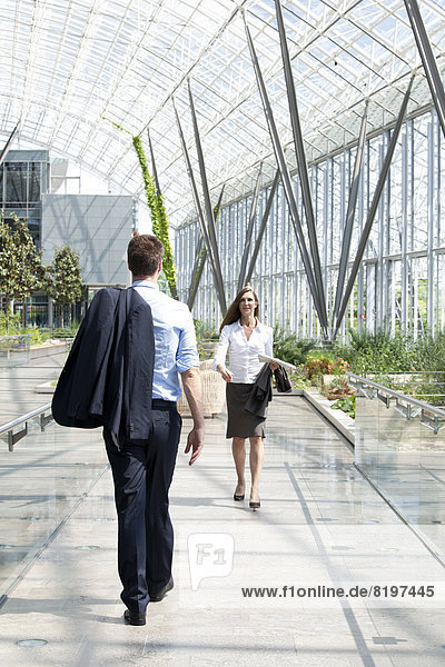 Businessman and businesswoman walking at modern office building