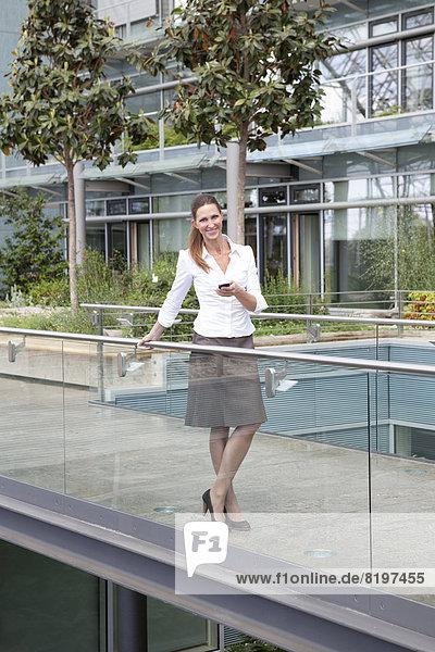 Geschäftsfrau mit Handy auf Steg