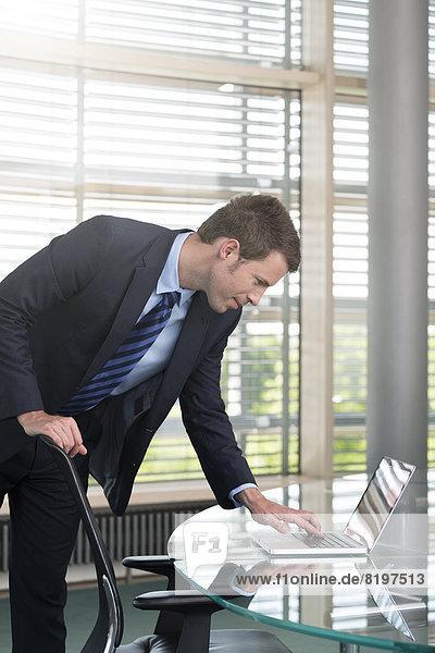 Deutschland  Hannover  Geschäftsmann mit Laptop am Konferenztisch