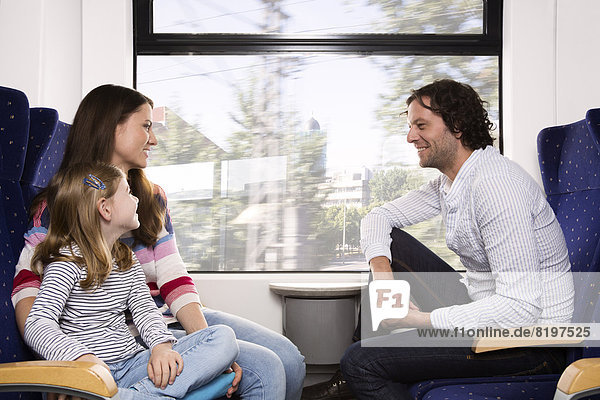 Germany  Brandenburg  Family traveling in train  smiling