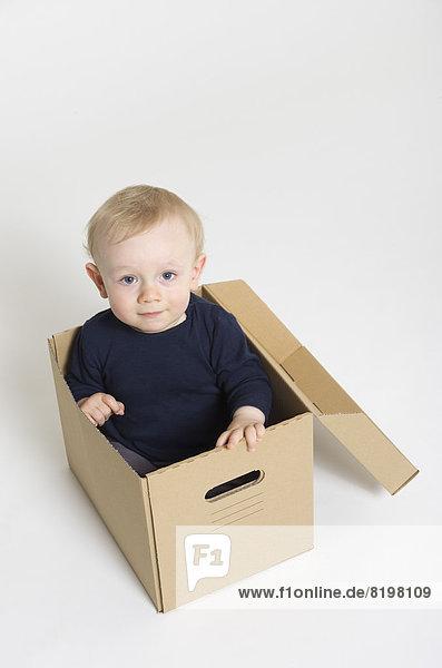 Portrait of baby boy sitting in box  smiling