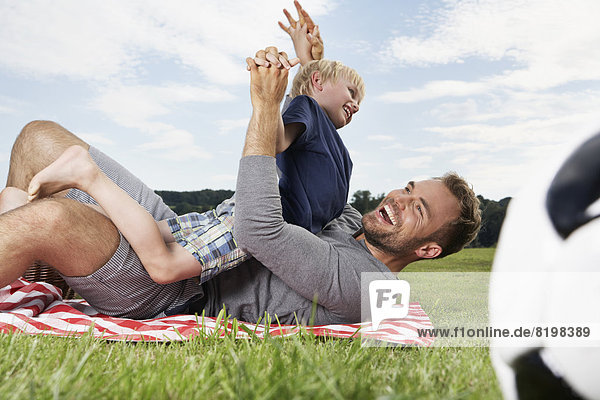 Germany  Cologne  Father and son playing around on picnic blanket