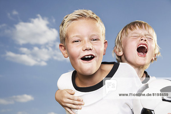 Two boys playing football  wearing football shirts
