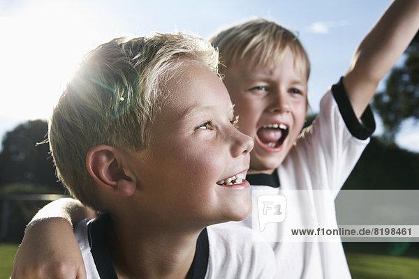Zwei Jungen  die Fußball spielen  tragen Fußballshirts.