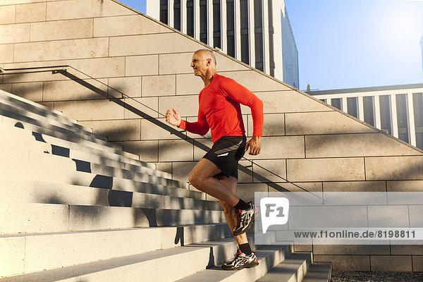 Älterer Sportler  der nach oben rennt.