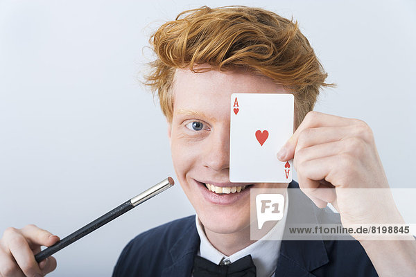Portrait of young man showing magic of cards,  smiling