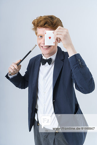 Portrait of young man showing magic of cards