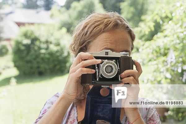 Reife Frau beim Fotografieren mit der Kamera
