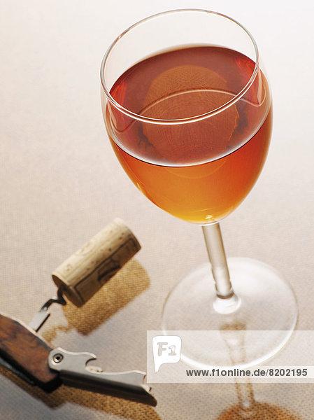 Ein Glas Rosé  Wein  daneben liegt ein Korkenzieher Ein Glas Rosé, Wein, daneben liegt ein Korkenzieher