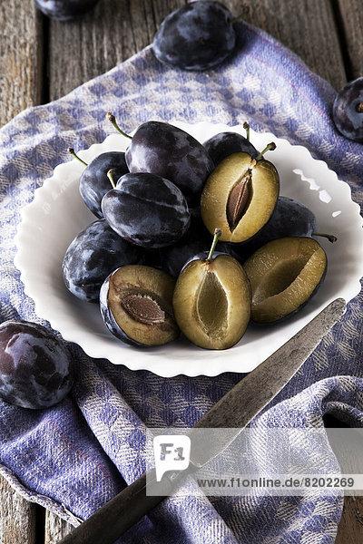 Frische Zwetschgen (Prunus domestica) auf Teller  Messer  Küchentuch