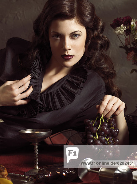 Woman posing on a festive table with grapes in her hand