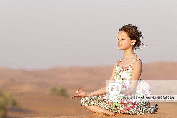 Mädchen meditieren in der Wüste