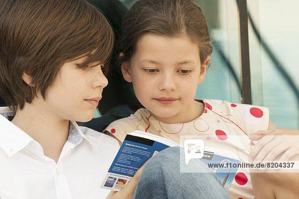 Bruder und Schwester lesen gemeinsam den Ratgeber