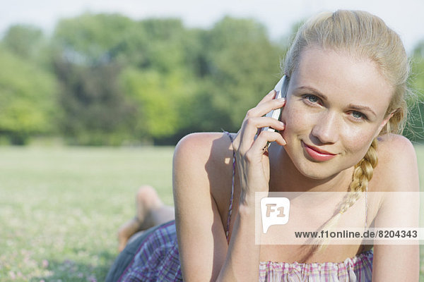 Junge Frau auf Gras liegend mit Handy  Portrait