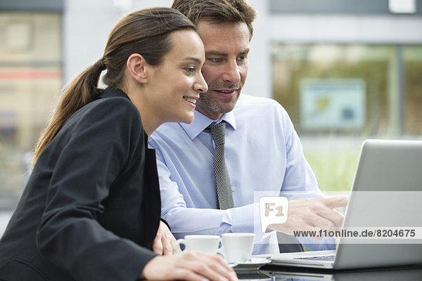 Geschäftsfreunde  die gemeinsam mit einem Laptop im Freien arbeiten.