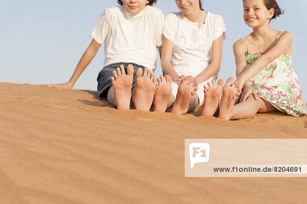 Kinder sitzen auf einer Sanddüne