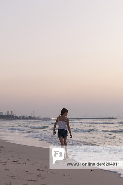 Girl walking on beach  looking at sea