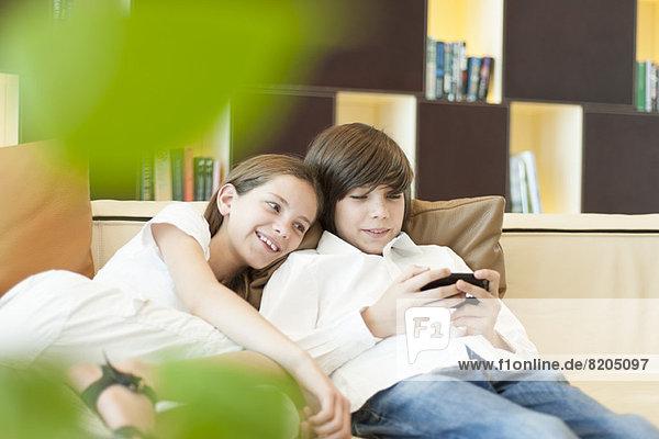 Bruder und Schwester schauen gemeinsam aufs Handy