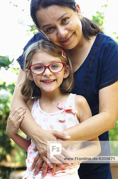 Außenaufnahme  Frau  umarmen  Hispanier  Tochter  freie Natur