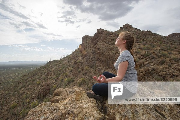 Woman meditating in desert  Tucson AZ.