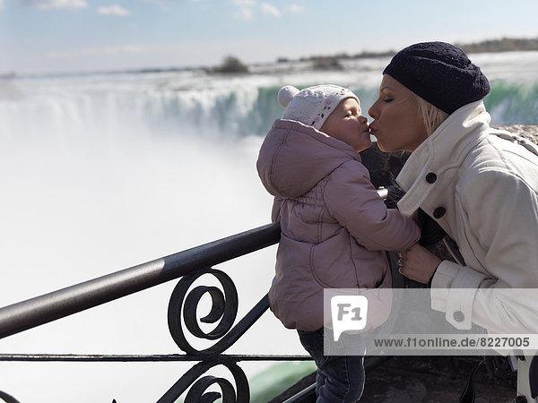 Mutter küsst ihre Tochter  2 Jahre  an den Niagarafällen