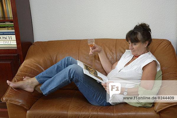 Frau  Mitte 60  mit einem Glas Wein beim Lesen