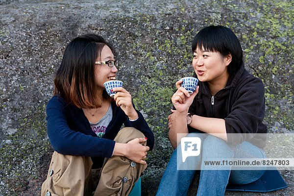 Smiling young women with tea cups