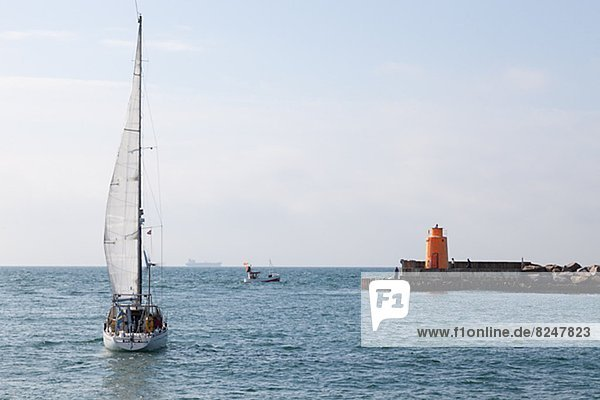 Sailing boat on sea  lighthouse in background