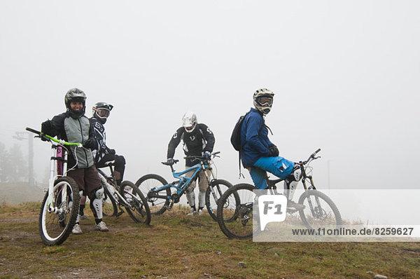 Portrait von Freunden mit Fahrrädern am Berg