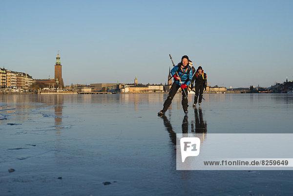 Mann und Frau beim Schlittschuhlaufen gegen den klaren Himmel