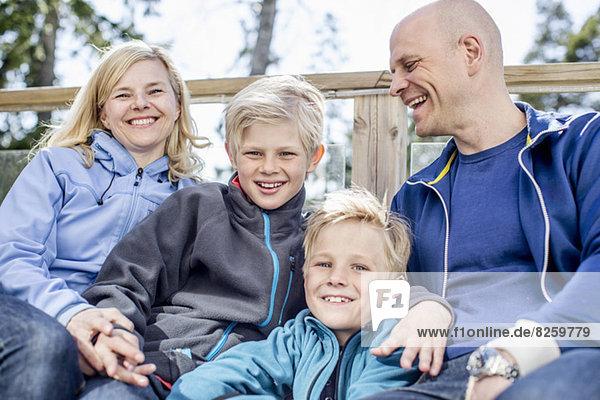Portrait von glücklichen Jungen mit Mutter und Vater im Freien