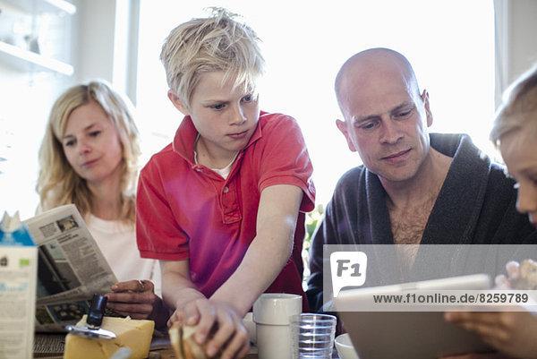 Mann und Söhne benutzen digitale Tabletten  während die Mutter am Esstisch Zeitung liest.