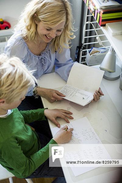 Hochwinkelansicht der Mutter  die dem Sohn bei den Hausaufgaben am Tisch hilft.