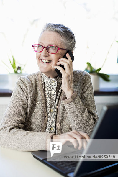 Happy senior woman using mobile phone while sitting with laptop on table