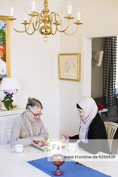 Junge Heimpflegerin mit einer älteren Frau  die zu Hause Ludo spielt.