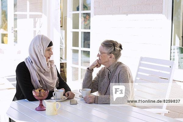 Hausfrau und Seniorin beim Kaffeetrinken auf der Veranda