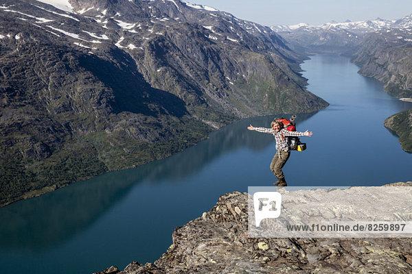 Porträt einer fröhlichen Kletterin mit ausgestreckten Armen im Stehen auf einem Felsen