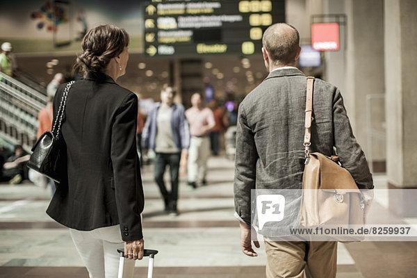 Geschäftsleute mit Gepäck zu Fuß auf dem Bahnhof