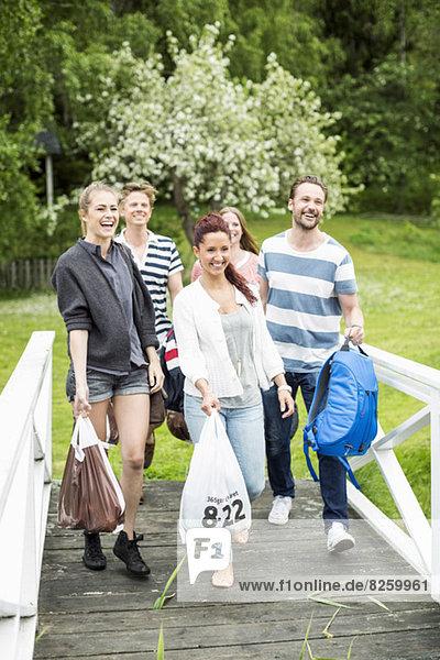 Gruppe von glücklichen Freunden mit Gepäck  die auf einer Promenade im Park spazieren gehen.