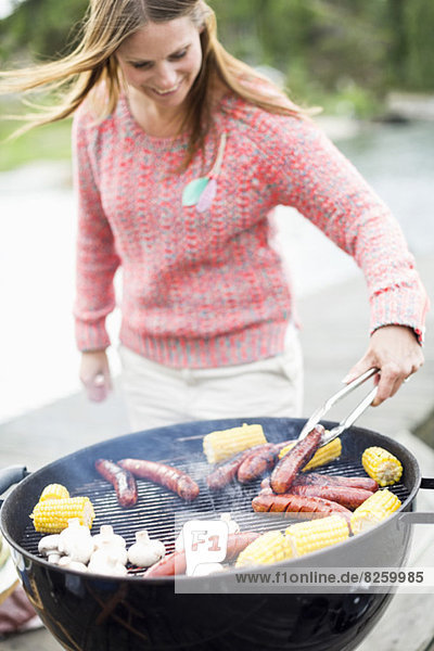 Mittlere erwachsene Frau beim Grillen im Freien