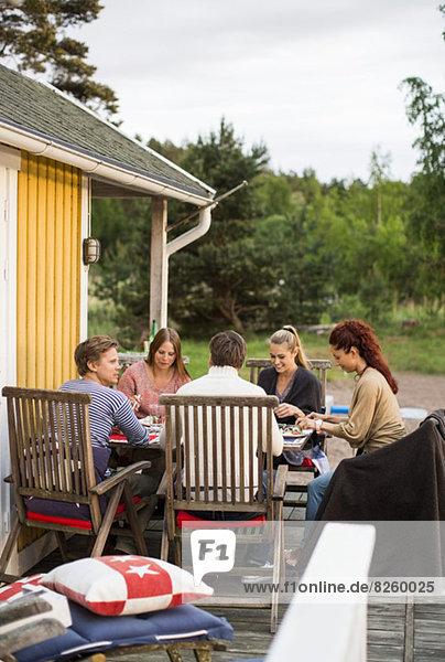 Gruppe von Freunden sitzt am Esstisch vor dem Sommerhaus