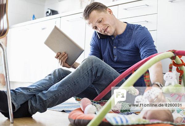 Vater mit digitalem Tablett und Handy beim Betrachten des Babys auf der Matte in der Küche