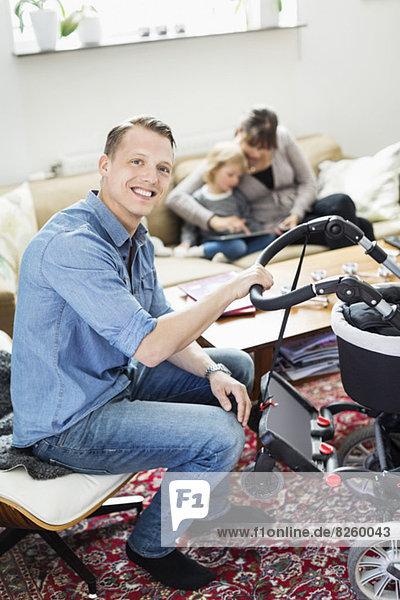Porträt eines glücklichen Mannes mit Kinderwagen im Wohnzimmer mit Familie im Hintergrund