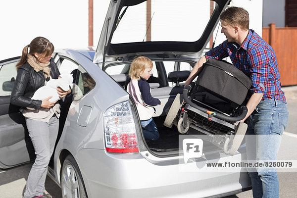 Eltern mit Kindern  die auf der Straße ins Auto steigen.