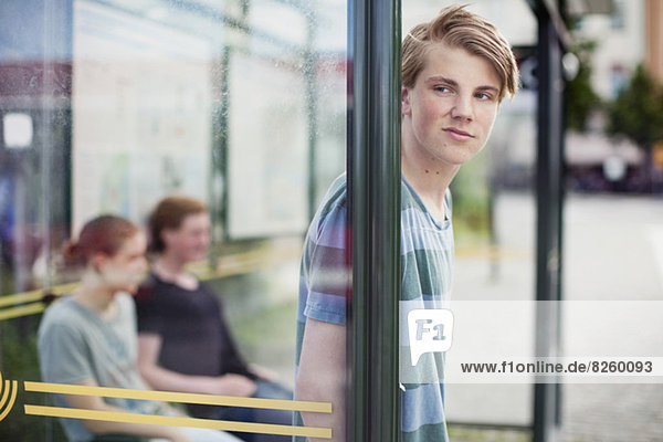 Young man waiting with friends at bus stop