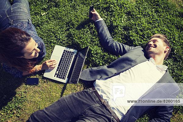 Großer Blickwinkel auf Geschäftsleute mit Laptop auf Gras im Park
