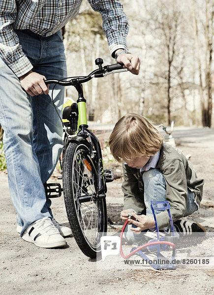 Junge füllt Fahrradreifen mit Fußpumpe während Vater auf der Straße steht